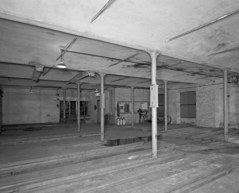 Interior. View from NE within high mill at ground floor level, showing vaulted cast-iron framed fire-proof structure, and office added after conversion of site to bonded (whisky) warehouse.