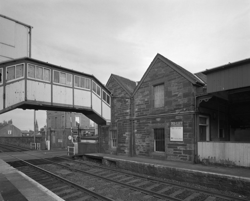 View from north west of rubble-built station offices, and wooden overbridge (left)