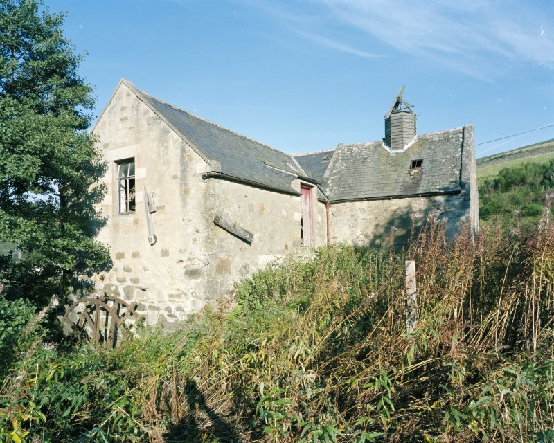 General view of mill from E, showing mill range (left) and kiln (right), also showing the water wheel on the SE gable of the mill.