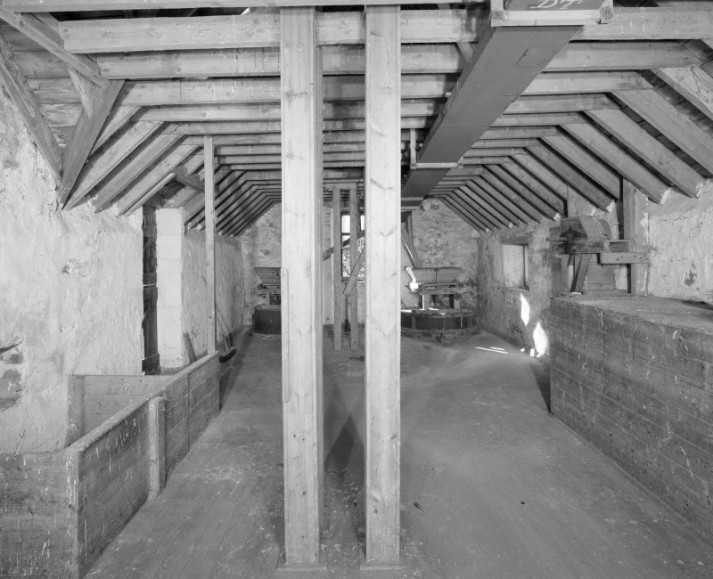 Interior. View at upper level of mill, showing two pairs of millstones in background.