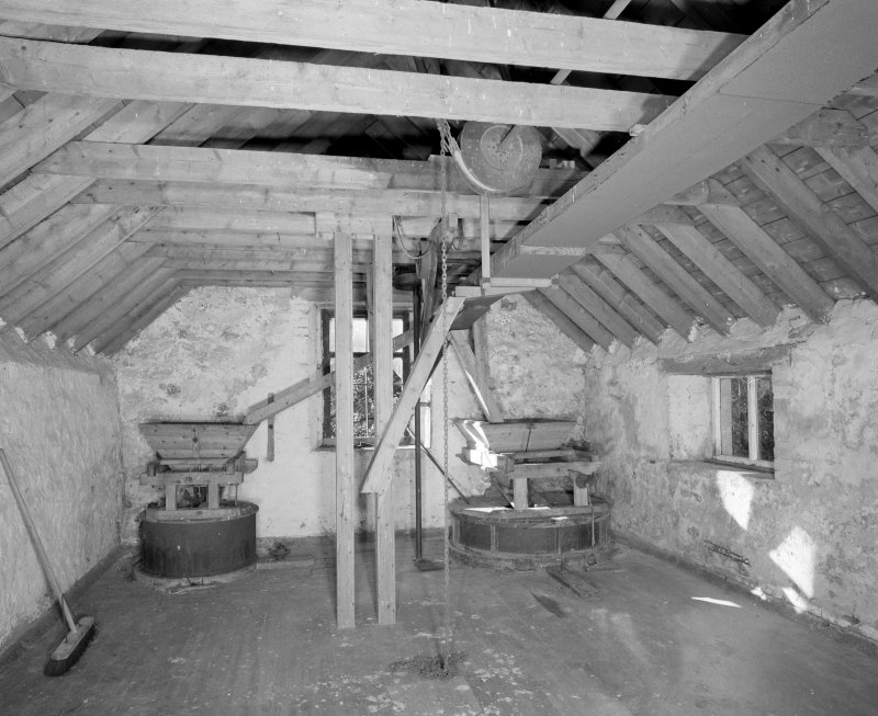 Interior. View at upper level of mill, showing two pairs of millstones.