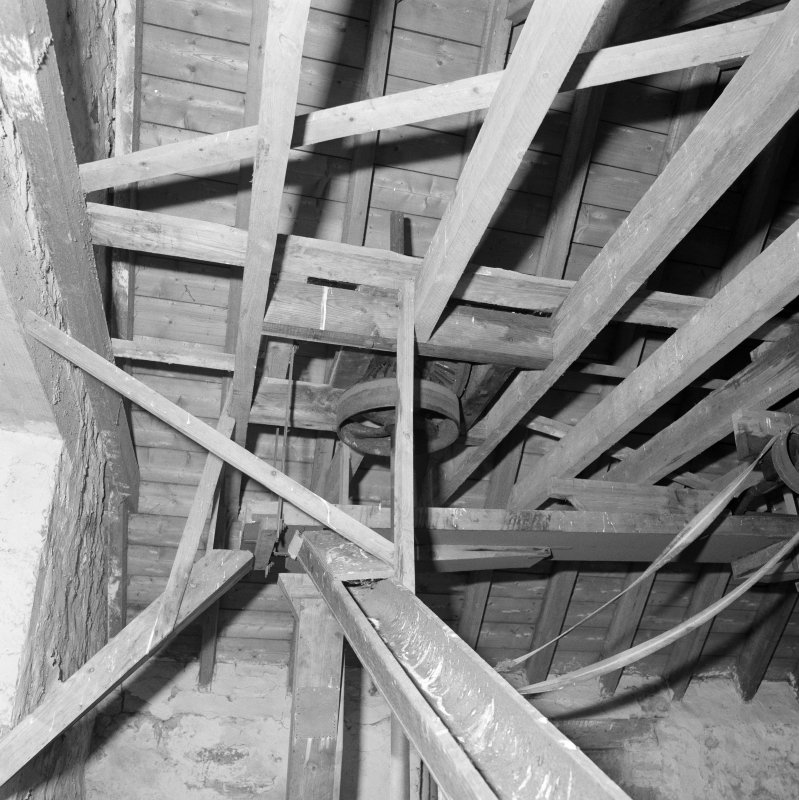 Interior View of roof space, showing part of vertical line-shaft and flat-belt pulley (with gears above), and adjacent bucket elevators and chute (foreground).