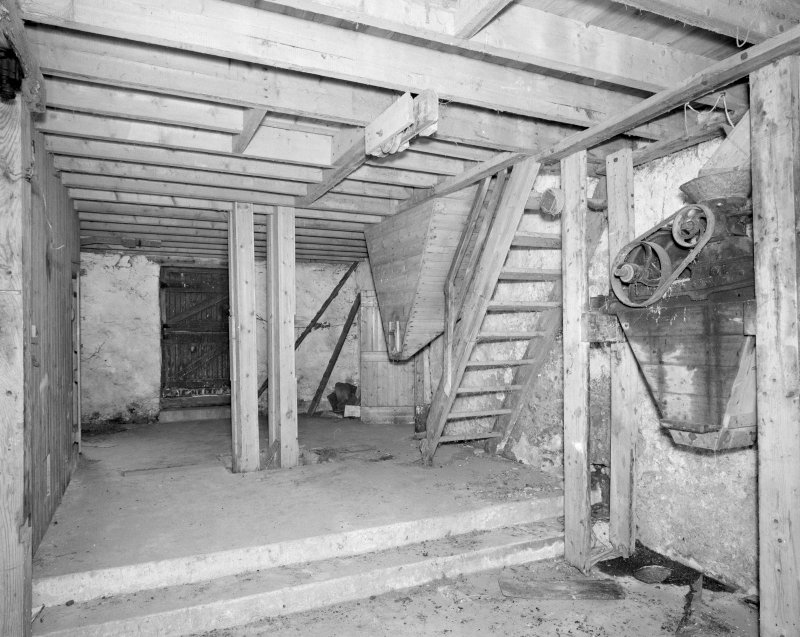 Interior. View at ground-floor level, showing wooden stair and the base of a wooden hopper and bucket elevator (centre left).