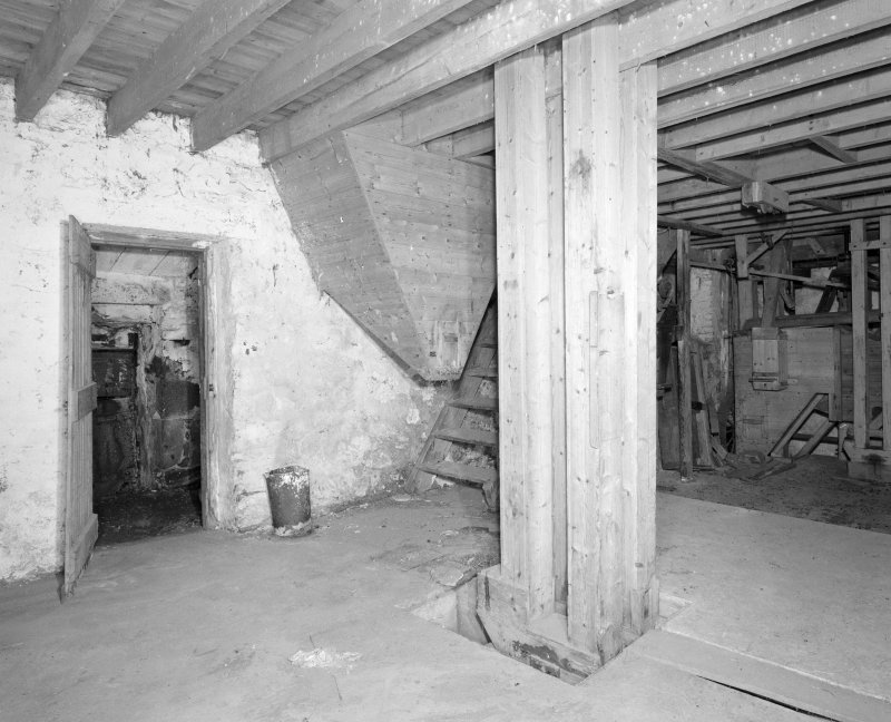 Interior. View at ground-floor level, showing wooden stair and the base of a wooden hopper, and bucket elevator (centre).