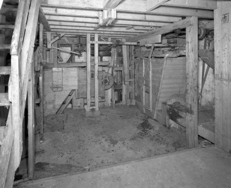 Interior. View at ground-floor level, showing winnowing machine (centre), with machinery of gear cupboard partially visible behind.