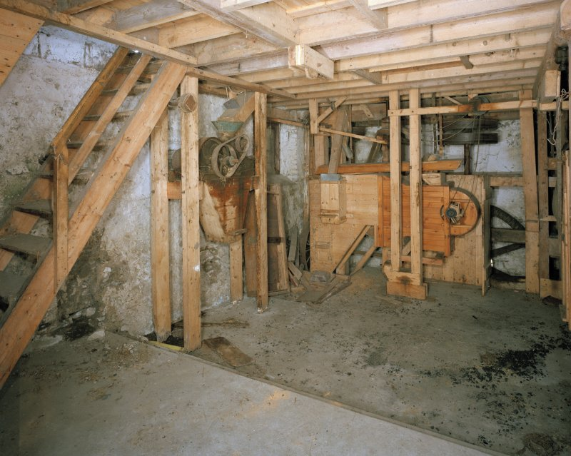 Interior. View at ground-floor level, showing winnowing machine (centre right), with machinery of gear cupboard partially visible behind.