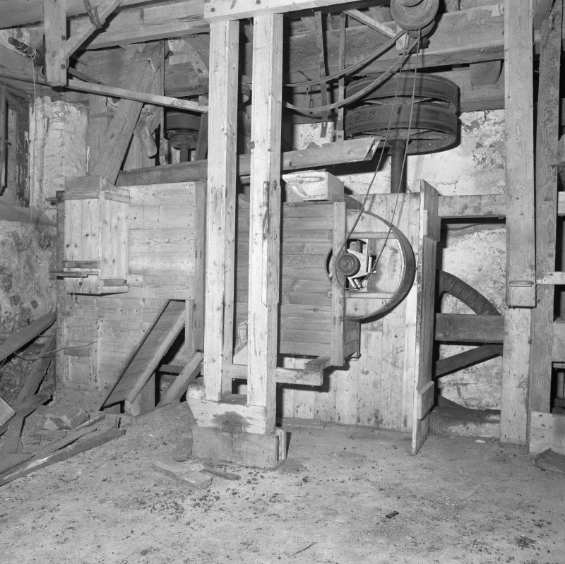 Interior. View of ground-floor level, showing winnowing machine (centre), with machinery of gear cupboard partially visible behind.