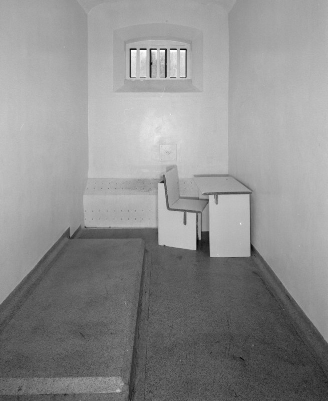 Detail of basement punishment cell with cardboard furniture