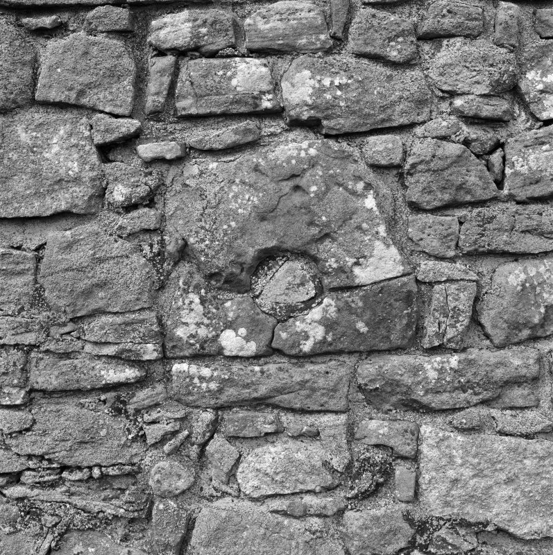 Detail of stone with blocked circular opening in East wall.