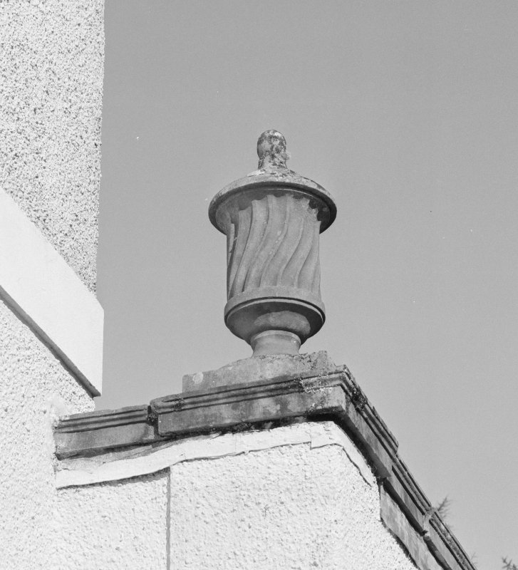 Detail of lidded urn on corner of flat-roofed wings