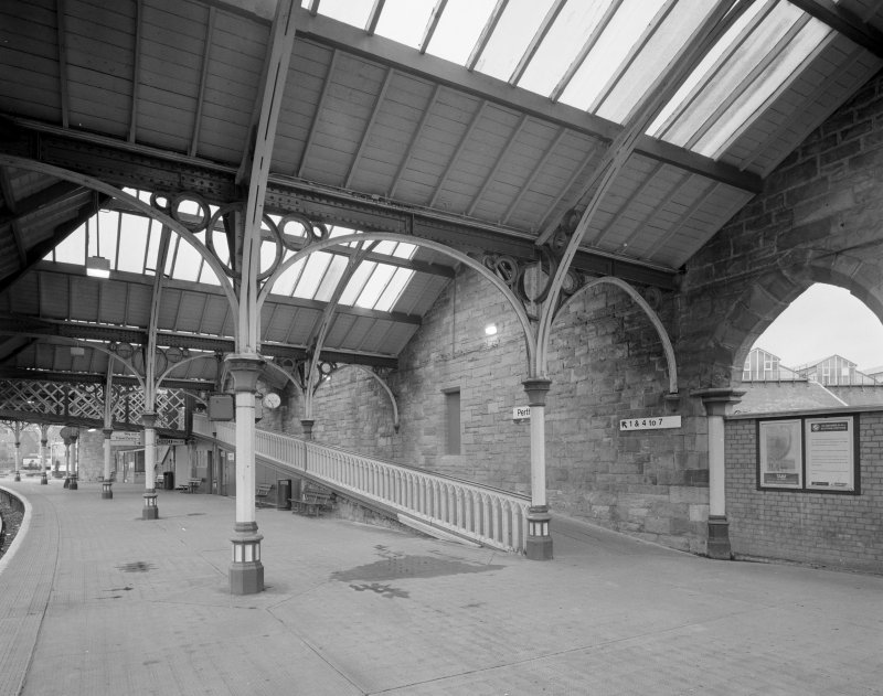 Perth, Leonard Street, General Station Platform 2: view from north east showing details of steel-framed glazed canopy (supported on ornate cast-iron columns), and ramp (with gothic-style cast-iron ballustrade) leading to footbridge