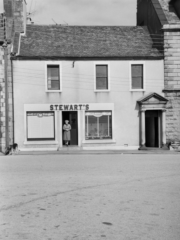 View of 18 North Main Street, Wigtown, from south east, showing shopkeeper at Stewart's shoe shop.