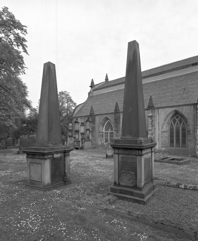 View of two obelisk monuments to South of church.