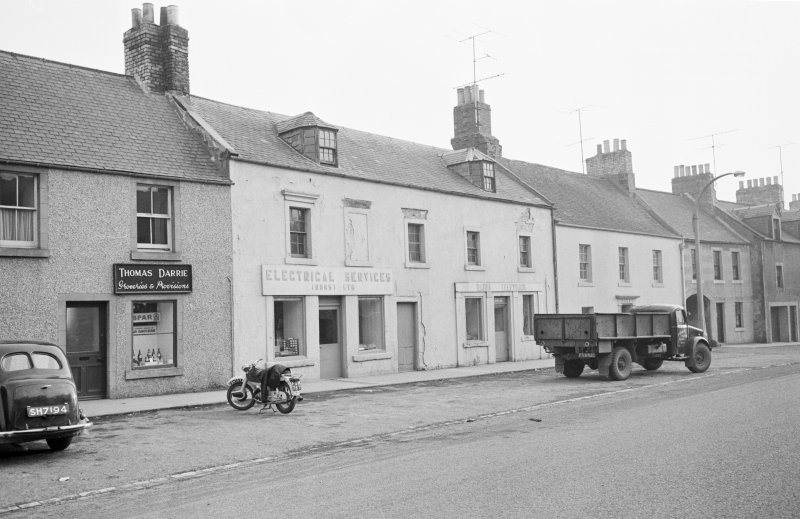 General view from north of 23-29 Newtown Street, Duns, showing the premises of Thomas Darrie groceries and provisions and Dursi Ltd Electrical Services