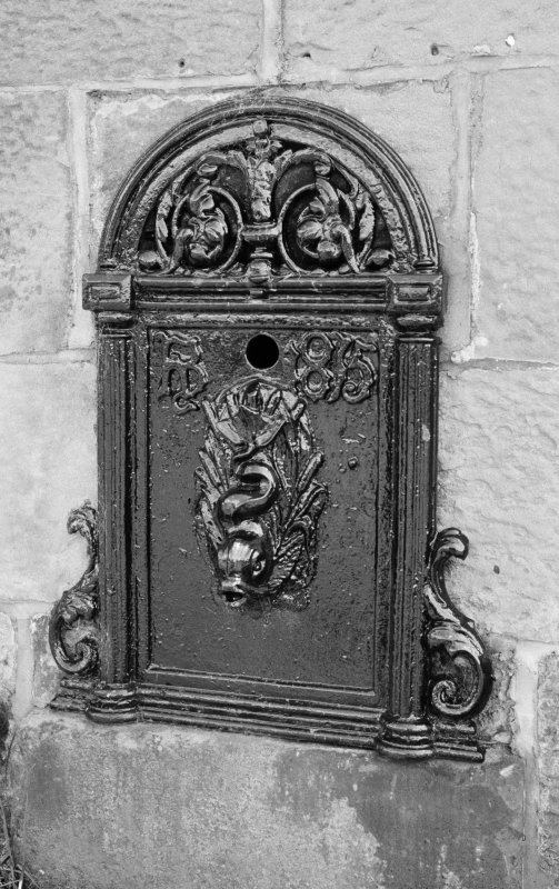 Detail of cast-iron water pump with dolphin spout by entrance to Allanton Old Fire Station.