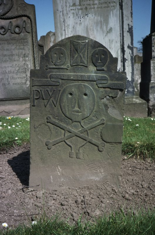 View of headstone 1711 to Patrick Wear, weaver, with primitive head and cross bones, and initials P W, Arbroath Abbey Churchyard.