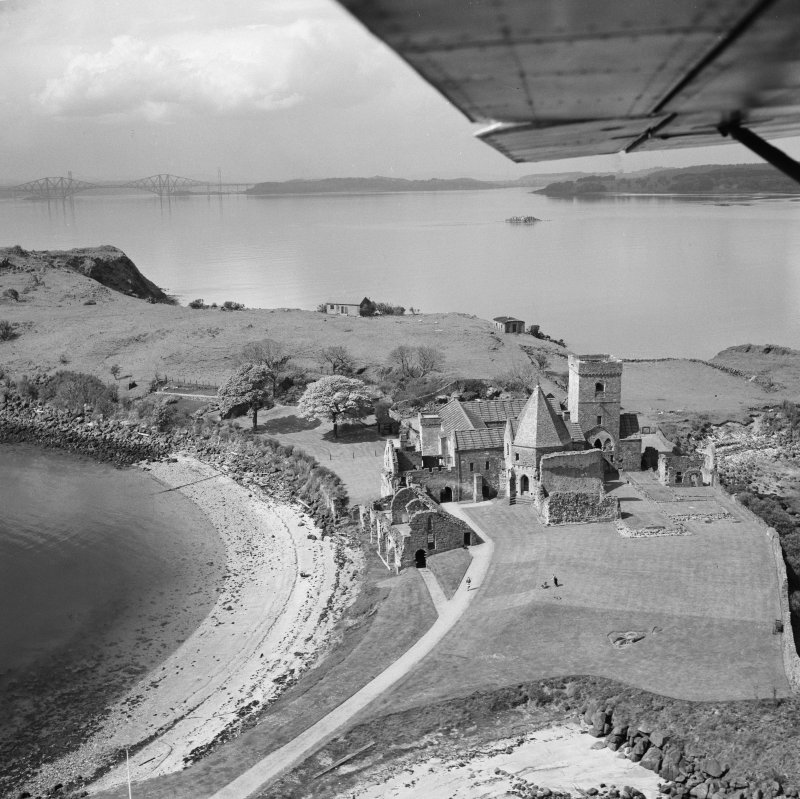 Oblique aerial view of Inchcolm Abbey showing the Forth Bridge in the distance.