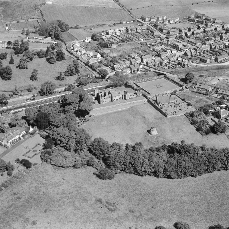 Oblique aerial view of Aberdour village, showing Aberdour Castle and dovecot, and St Fillan's Church