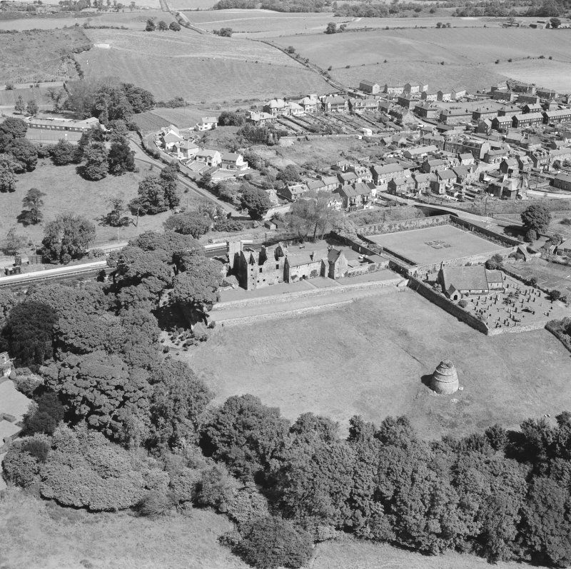 Oblique aerial view of Aberdour village, showing Aberdour Castle and dovecot and St Fillan's Church