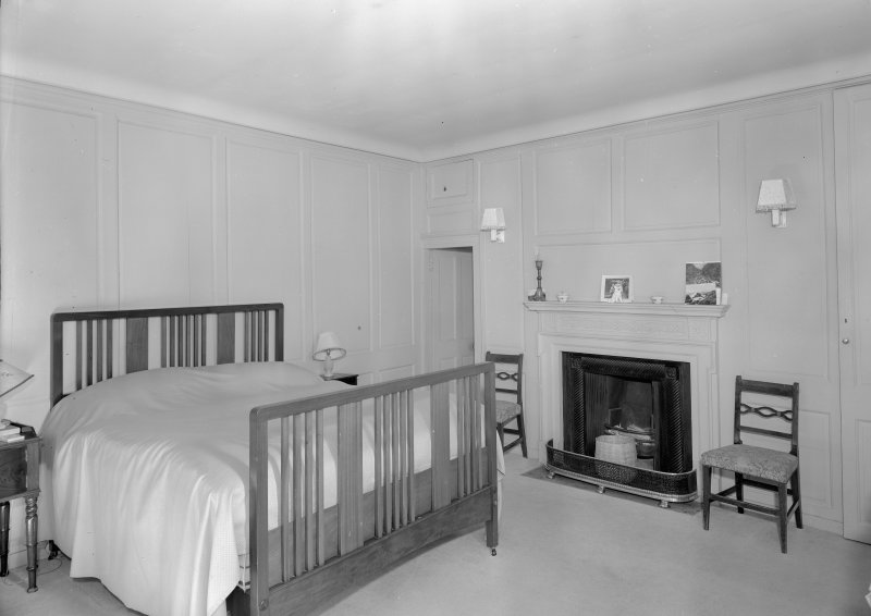 Interior view of Corsindae House showing panelled bedroom with fireplace.