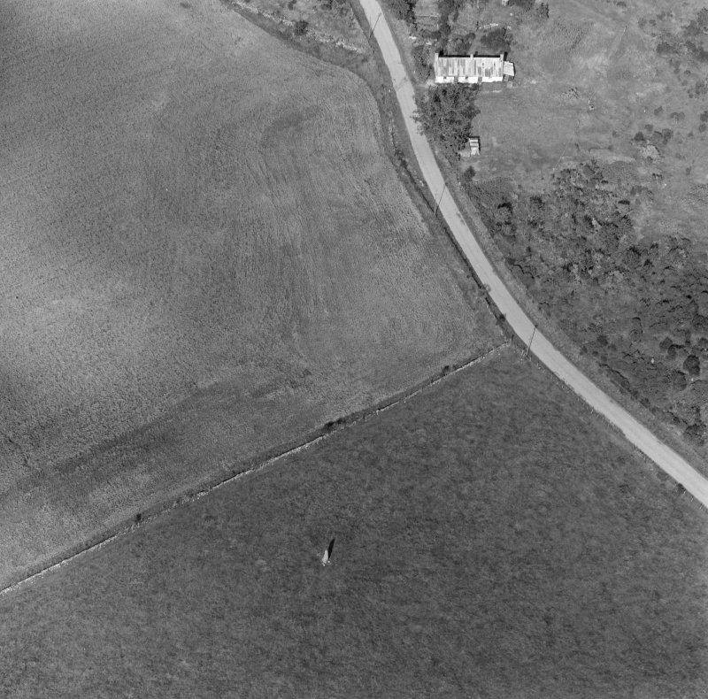 Oblique aerial view of Clach Chairidh Pictish symbol stone, Ederton and the site of Carriblair stone circle.