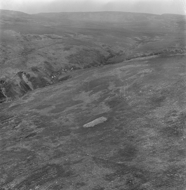 Oblique aerial view centred on the chambered cairn at Carn Ban, Arran.