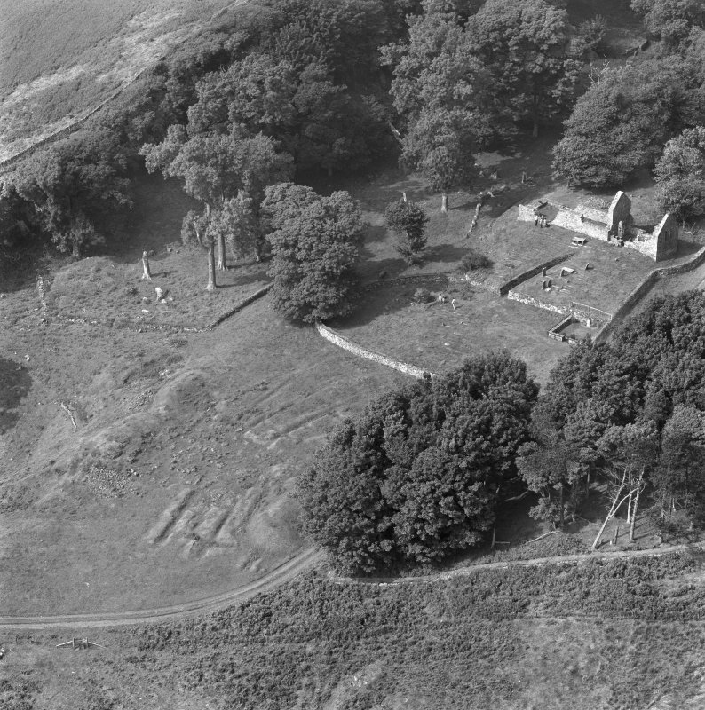 Oblique aerial view centred on the remains of St Blane's Church and burial ground, Bute, taken from the N.
