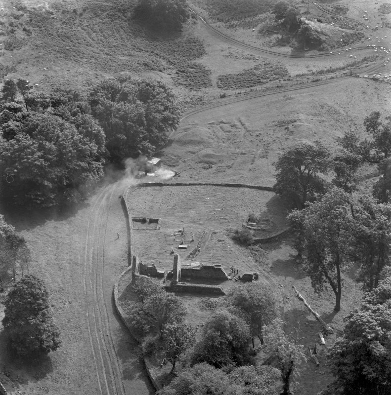Oblique aerial view centred on the remains of St Blane's Church and burial ground, Bute, taken from the SE.