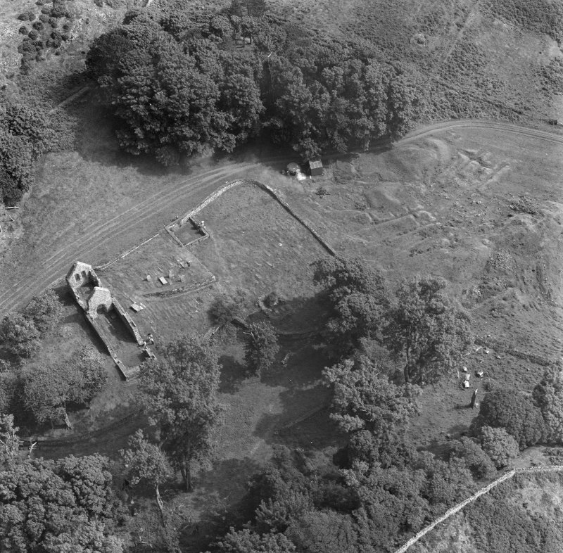 Oblique aerial view centred on the remains of St Blane's Church and burial ground, Bute, taken from the WNW.