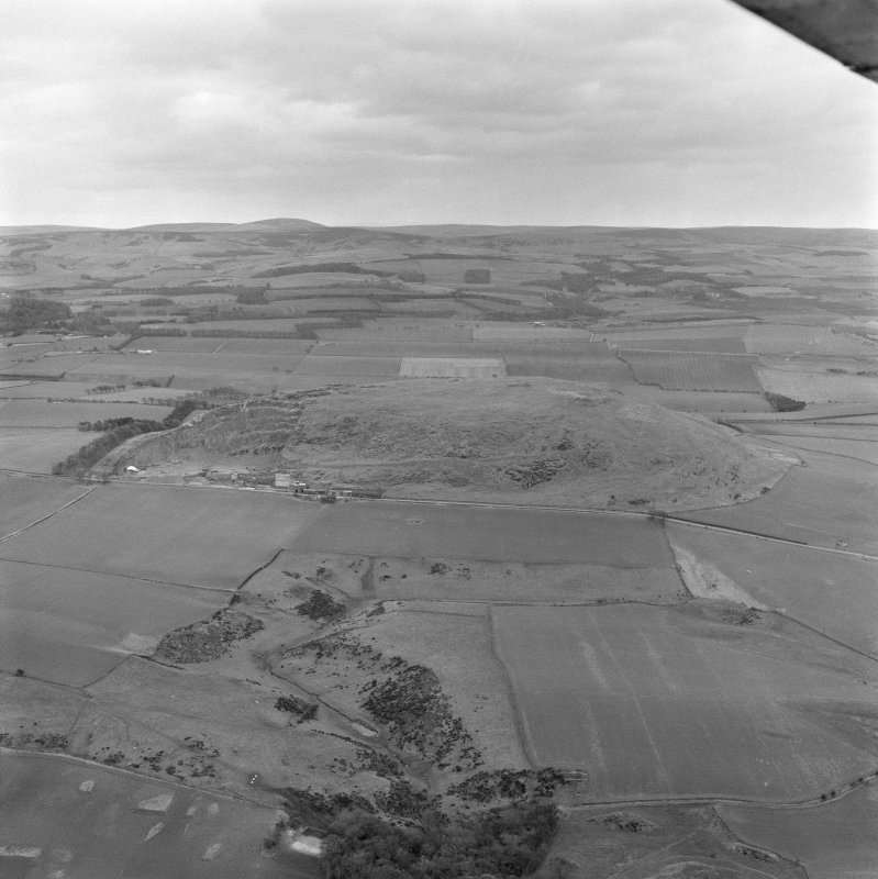 Oblique aerial view of the remains of Traprain Law fort, looking SE.