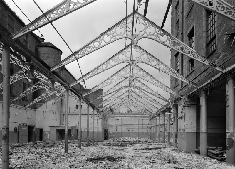 Interior view of Ward Mills, Dundee showing ornate cast iron trusses during demolition.