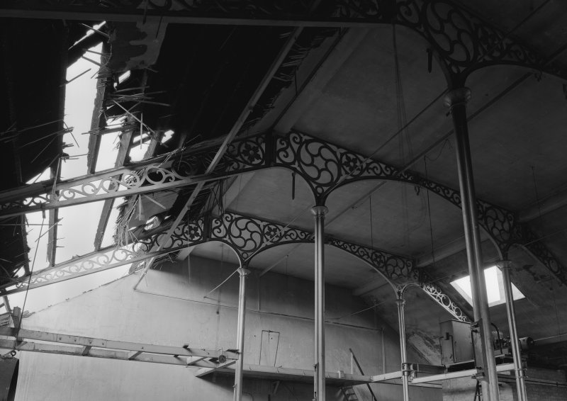Interior view of Ward Mills, Dundee showing detail of ornate cast iron trusses during demolition.