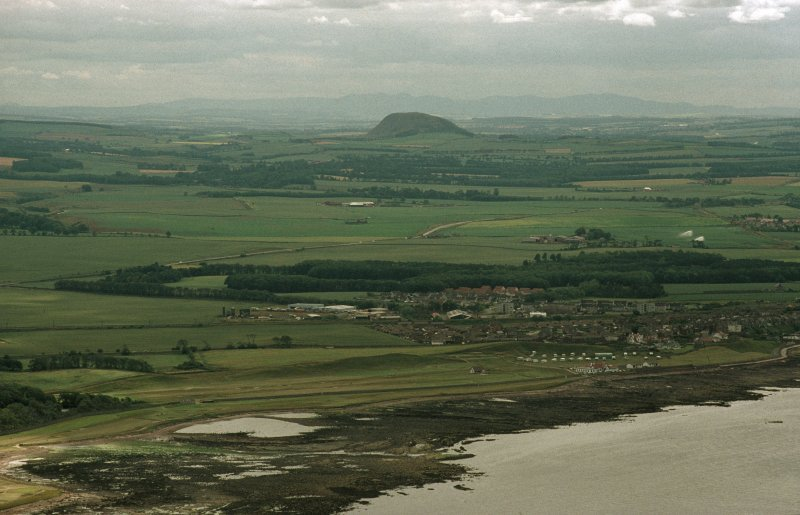 Oblique aerial view taken from the NE, looking SW from the sea and across the town of Dunbar (NT67NE 96), with Traprain Law fort (NT57SE 1) in the distance.