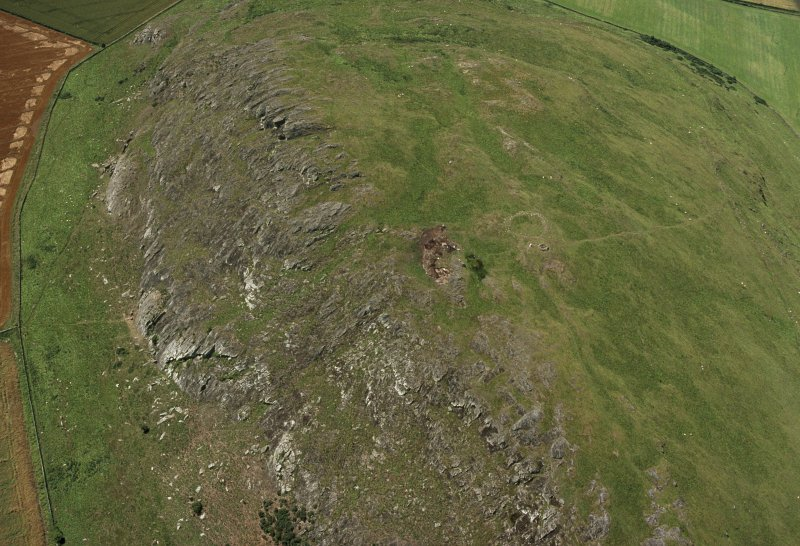 Oblique aerial view of Traprain Law fort centred on summit excavations undertaken in July 1997, taken from the NE.
