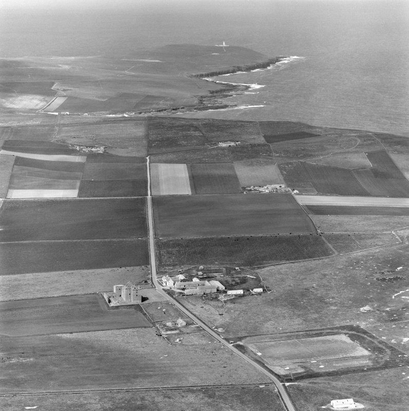 Oblique aerial view centred on the ruins of Noltland Castle, Westray with Noup Head Lighthouse visible in the background.