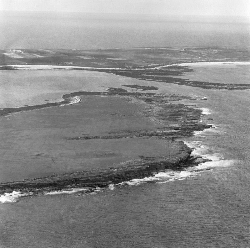 Oblique aerial view centred on the chambered cairn (south) on Holm of Papa Westray with Papa Westray visible in the distance.