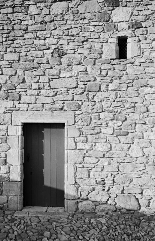 Detail of tithe barn, Foulden, showing stonework and door to rear.