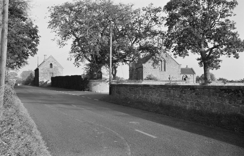 View of the tithe barn and church from the road.