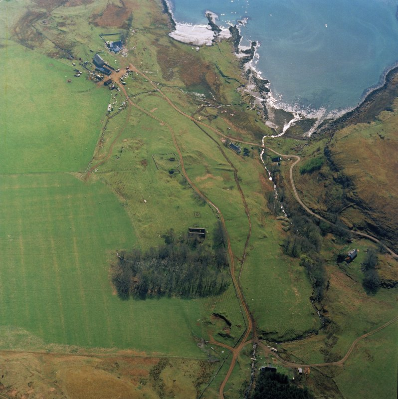 Oblique aerial view centred on the remains of the church with farmhouse, barn and farmsteading adjacent, taken from the N.