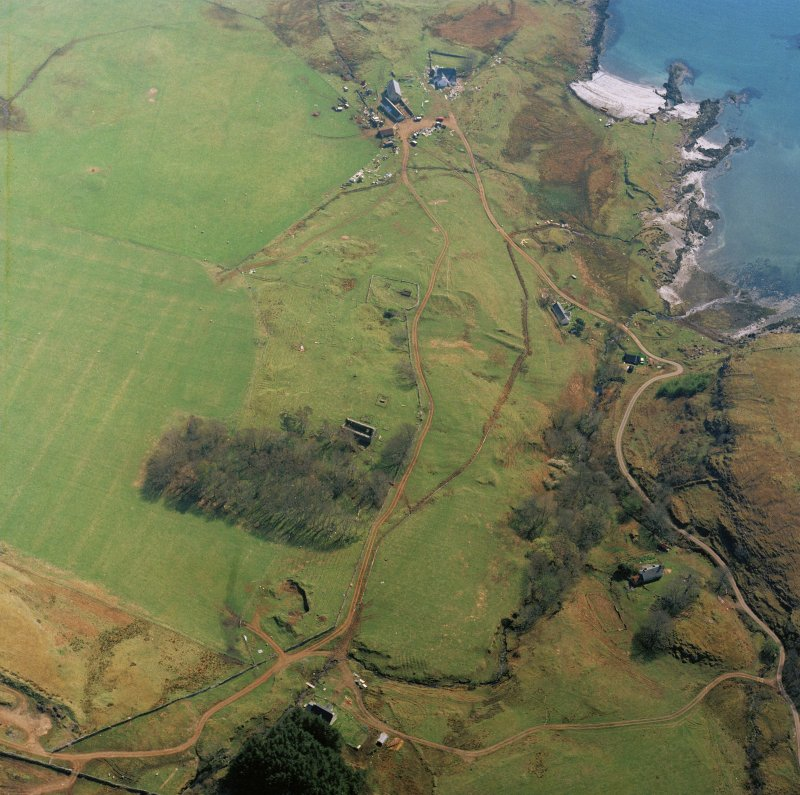 Oblique aerial view centred on the remains of the church with farmhouse, barn and farmsteading adjacent, taken from the NW.