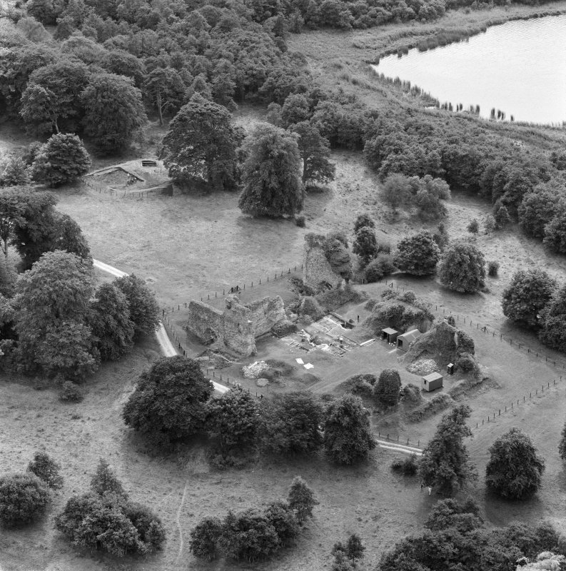 Oblique aerial view centred on Lochmaben Castle from NE, showing excavations in progress.