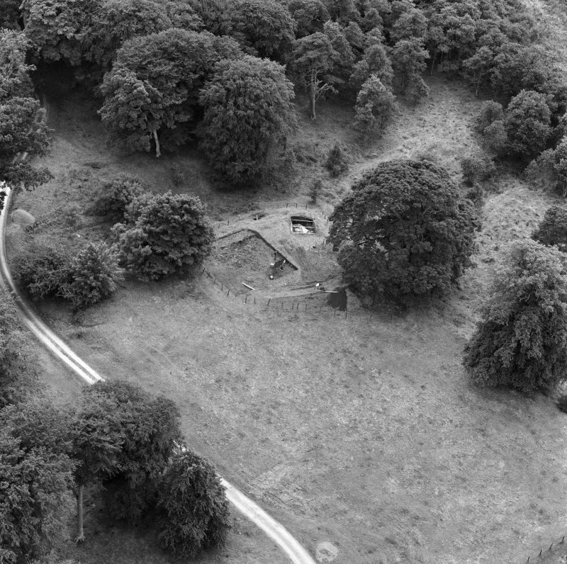 Oblique aerial view from NE showing excavations in progress at Lochmaben Castle.