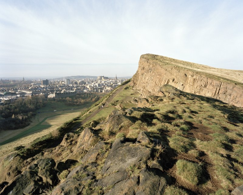 Holyrood Park: view of Salisbury Crags from S, with Edinburgh Castle in background