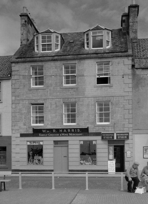 View of 29-30 Shore Street, Anstruther Easter, from SW, showing a grocer and wine merchant and a photographer studio.