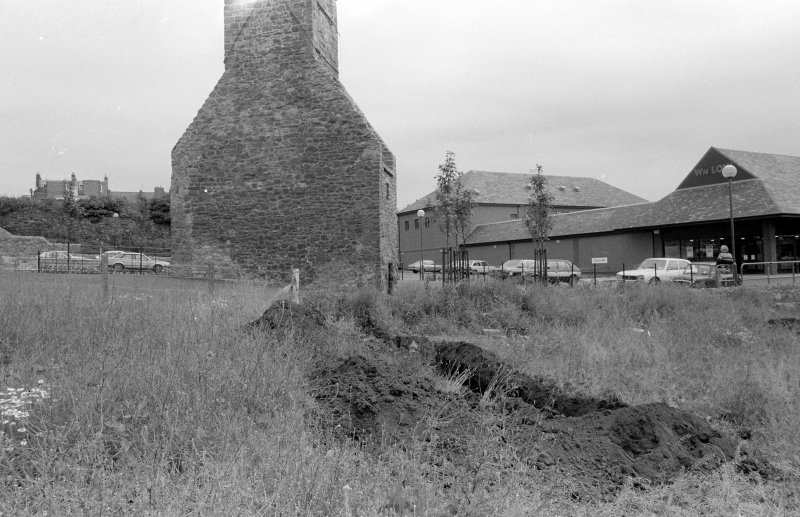 Excavation photograph : general view of trial trench 1 with doocot in background, looking east.