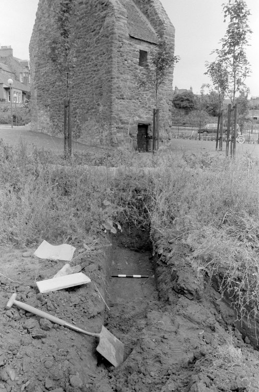 Excavation photograph : general view of trial trench 2 with doocot in background, looking north-east.