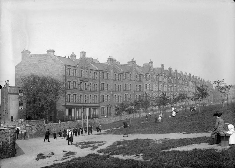 View of children and women in Holyrood Park, Edinburgh showing Royal Park Terrace in the background.