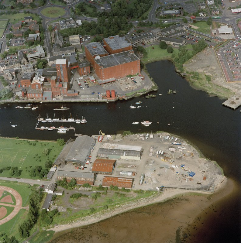 Oblique aerial view centred on the shipyard and whisky distillery, taken from the SSW.