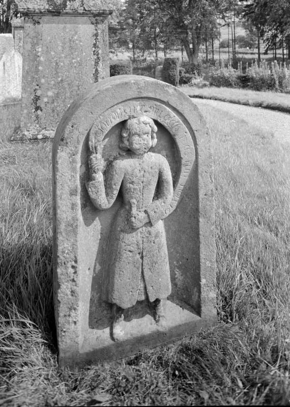 View of headstone of Cunningham showing youth in skirted suit with riband scroll overhead.