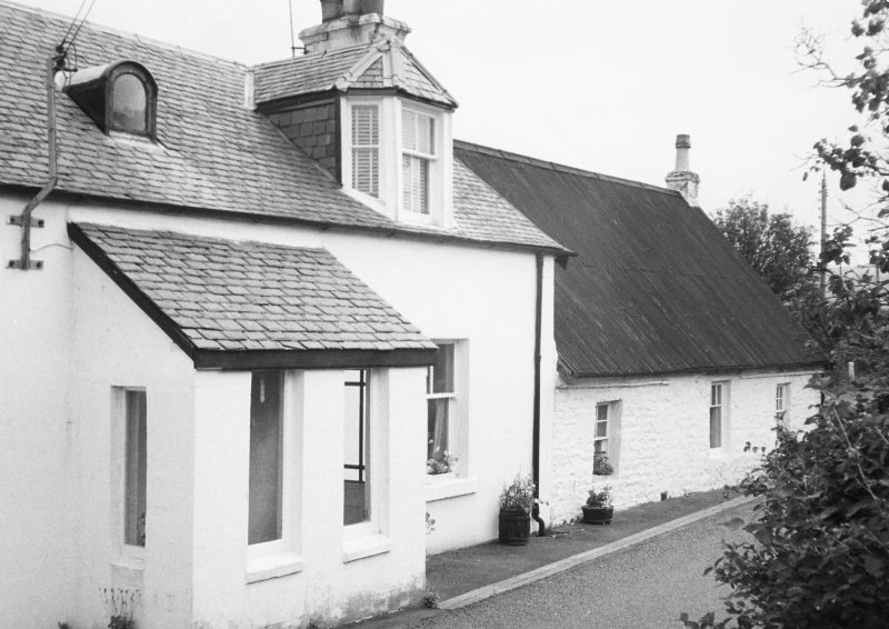 View of white-washed cottage and adjacent house.